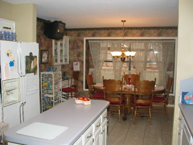 Long view of the kitchen with eating area in the background